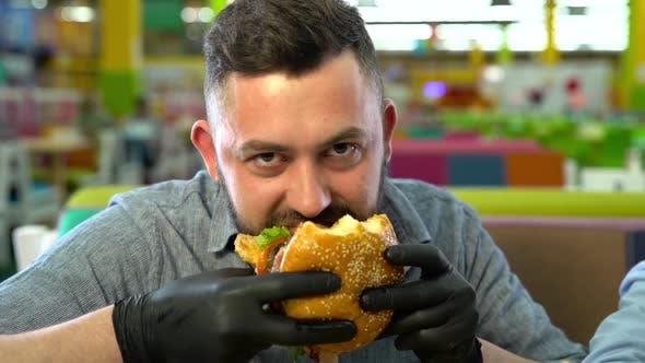 Thumbnail for Slow Motion of Father Eating Burger at Fast Food Restaurant