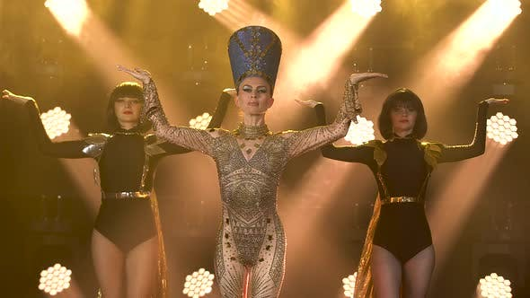 A Young Woman in a Cleopatra or Nefertiti Costume and Headdress Dancing with Two Women in a Dark
