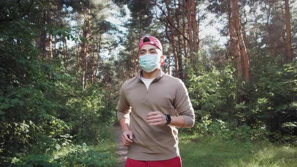 Asian Young Man are Jogging Outdoor in City Park and Wearing Protective Mask on Face for Stay in Fit