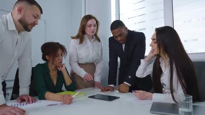 Multiethnic Startup Team Discussing Progress at Meeting