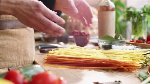 Thumbnail for Male Cook Throwing Bunch of Uncooked Spaghetti on Table