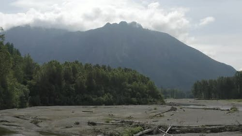 Flying Above Snoqualmie River Dried Out Riverbed Fallen Trees Huge Mountain Background