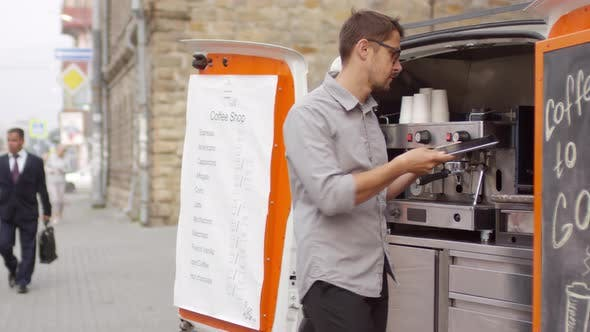 Idle Caucasian Barista Standing by Mobile Coffee Van in Street