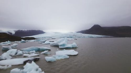 Icebergs Floating in Water and View of the Mountain Ranges With Patches of Snow