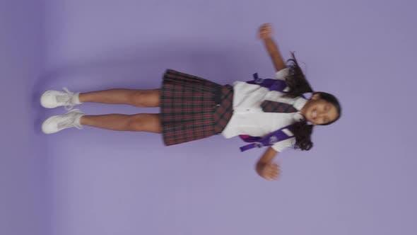 Возбужденный счастливая индийская школьница прыгает на фиолето