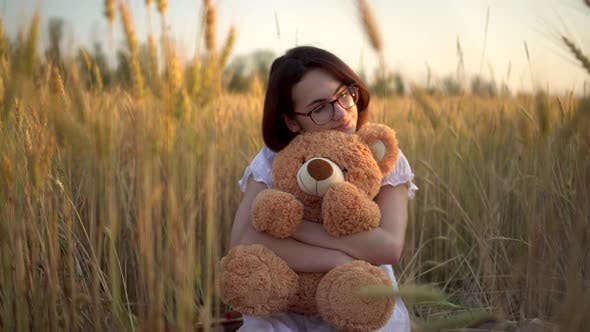 A Young Woman Sits in a Dried Wheat Field with a Teddy Bear. Girl Hugs a Teddy Bear in Hands Front