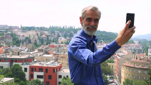 Thumbnail for Old Senior Man Photographs with Smartphone (Selfie) - City (Buildings) in Background