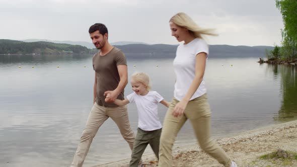 Family Walking by the Lake and Having Fun