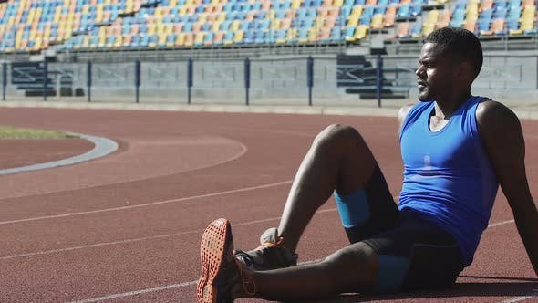 Thumbnail for Handsome Man in Sports Wear Sitting on Running Track Taking Breath and Resting