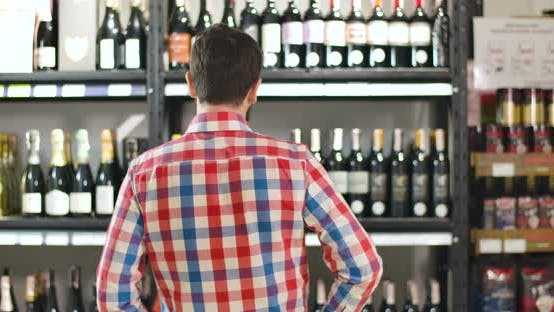 Thumbnail for Back View of Man Scratching Head As Looking at Shelves with Bottles of Wine. Confused