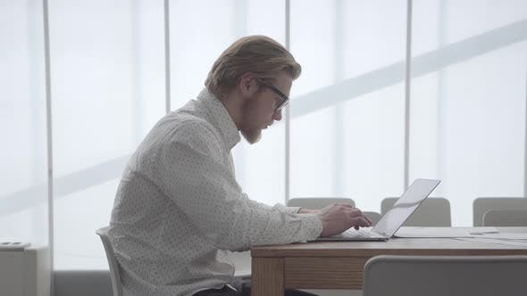 Thumbnail for Blond Thoughtful Man in Glasses Sitting at the Table in a Light Comfortable Office