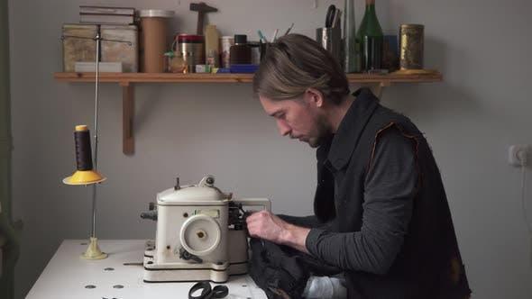 Male Tailor Sewing Fur on Furrier Machine in Workshop