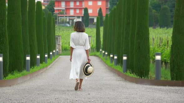 Thumbnail for A woman walking on a path with cypress trees while traveling at a luxury resort in Italy, Europe
