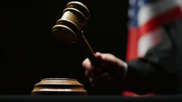 Thumbnail for Judge's Hand With Wooden Hammer Against American Flag Black Background In USA Court