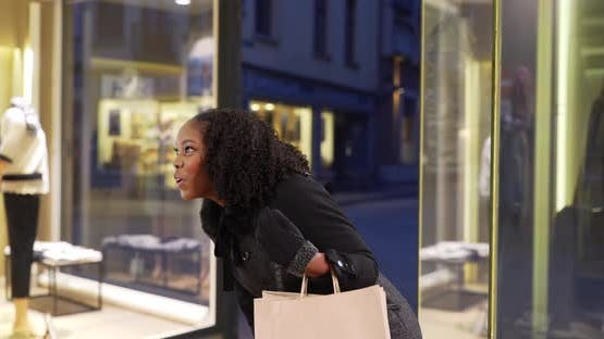 Black female carrying shopping bag looks at clothing store window in evening