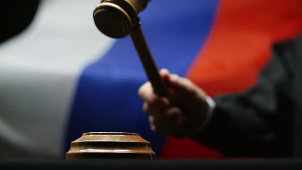 Cover Image for Judge With Gavel In His Hand Against Waving Russian Flag In Court Room