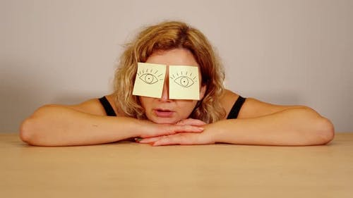 Young Woman Naps on Wooden Table with Stickers on Forehead