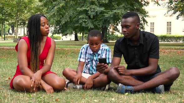 Thumbnail for A Black Family Sits on Grass in a Park, Looks at a Smartphone and Talks About Something