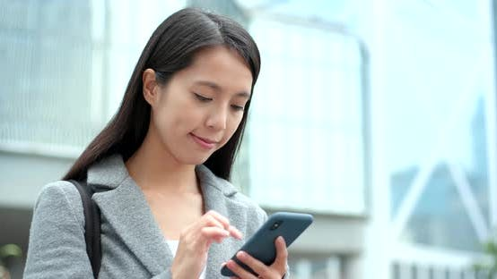 Cover Image for Businesswoman use of smart phone in city