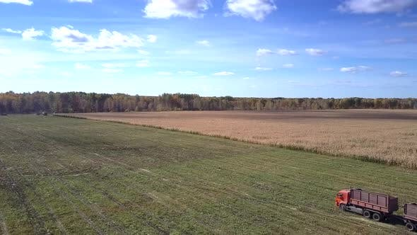 Thumbnail for Aerial View Truck with Empty Trailer Stands on Harvested Field