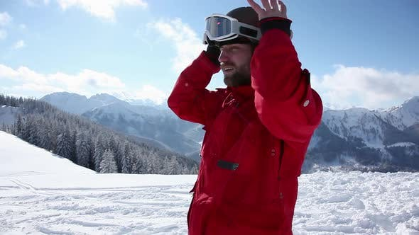 Thumbnail for Skier putting on helmet and goggles and moving off