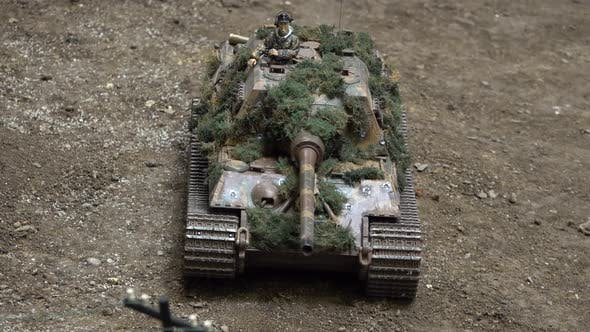 Thumbnail for An Exhibition of Army Car Models. A Camouflaged Tank Drives and Turns on a Model Dirt Road.