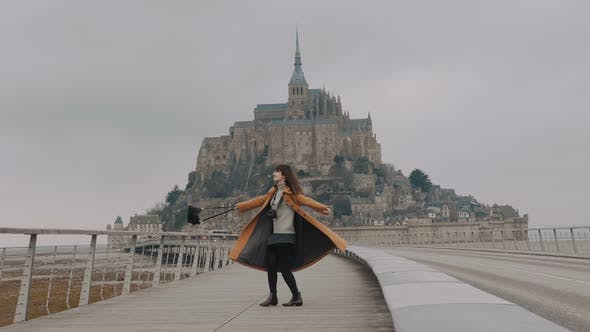 Beautiful Happy Freelance Blogger Woman Spinning with Arms Open, Posing at Amazing Mont Saint Michel