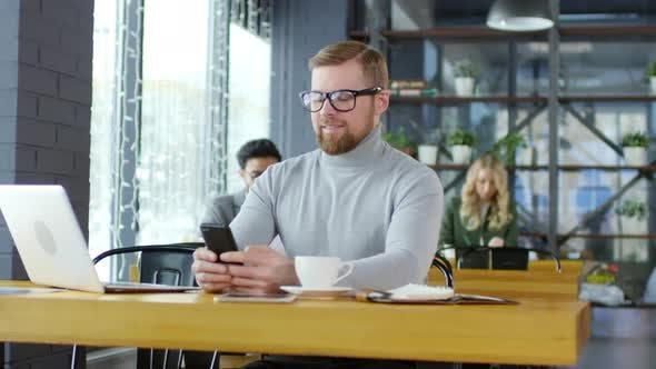 Thumbnail for Smiling Businessman Texting on Smartphone in Coffeeshop