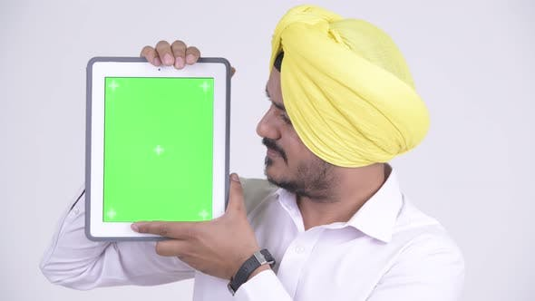 Thumbnail for Face of Happy Bearded Indian Sikh Businessman Showing Digital Tablet