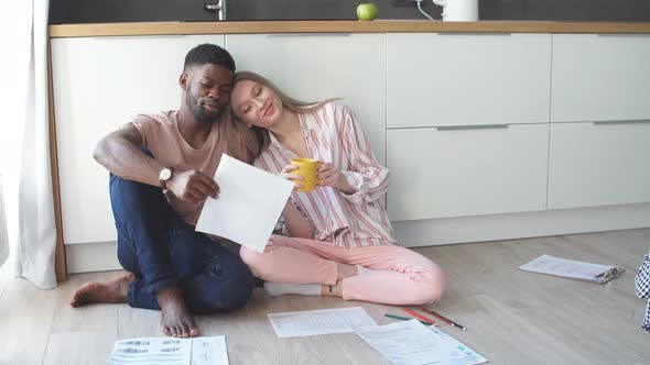 Thumbnail for Couple Doing Home Budget Accounting Sitting on Kitchen Floor at Home