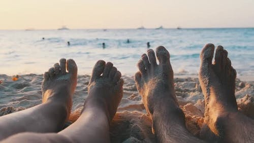 POV Feet of a Couple of Men and Women Lying on a Sandy Beach at Sunset By Ocean