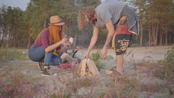 Thumbnail for Young Hipster Guy and His Girlfriend Making a Fire with Woods on the Background of Their Friend