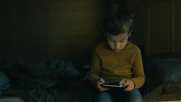Child with Cellphone Sitting on Bed at Home