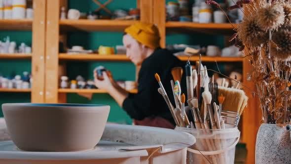 Thumbnail for Töpferwerkstatt - Verschiedene Instrumente für die Herstellung von Tongerichten - ein Mann geht in die Regale und