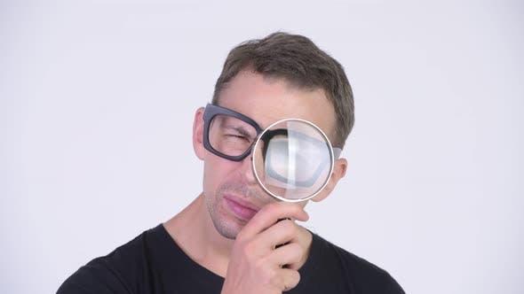 Thumbnail for Studio Shot of Nerd Man Using Magnifying Glass