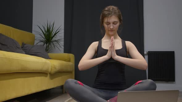 Young Woman Doing Yoga on Floor of Her Apartment