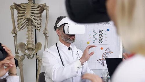 Attractive Considerate Doctor with Gray Hair and Beard Wearing Virtual Reality Glasses