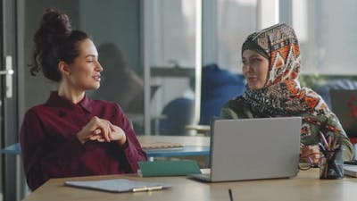 Businesswoman Talking with Female Colleague in Hijab