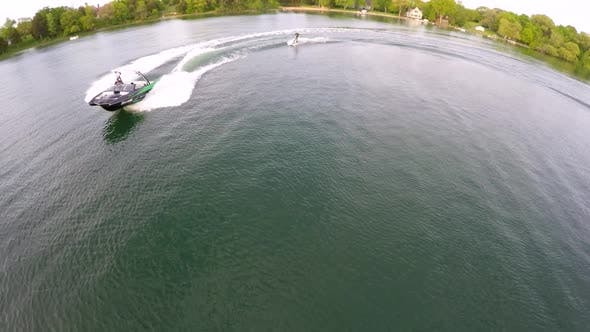 Thumbnail for Vue aérienne de drone œil d'oiseau d'un homme wakeboard derrière un bateau.