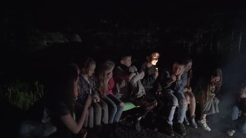 Teenager Telling Scary Story Using Flashlight on Face.