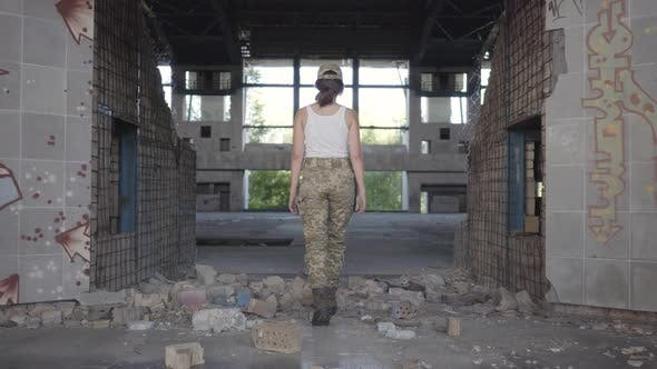 Cover Image for Confident Young Woman in Military Uniform Walking Slowly in Dusty Dirty Abandoned Building