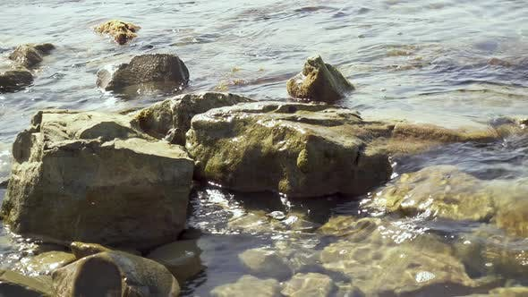 Thumbnail for Small Waves Roll on Rocks on the Shore