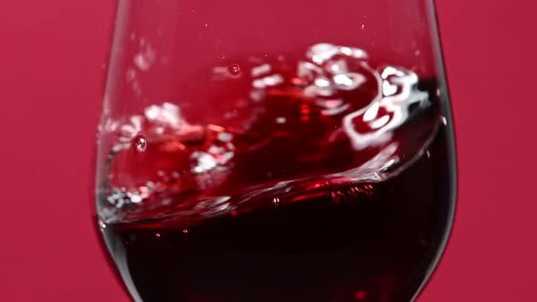 Thumbnail for Wirbelnder Rotwein im Weinglas über lila Hintergrund, Seitenansicht