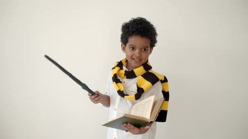 African American Kid Reading a Book and Holding Magic Wand