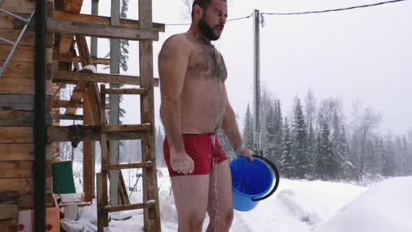 Thumbnail for Man pours a cold water on himself in winter forest