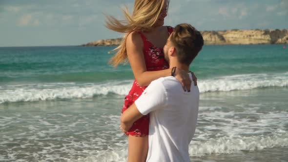 Thumbnail for Bearded Man Raised the Girl in Dress in His Arms and Spinning Around with Her at the Beach