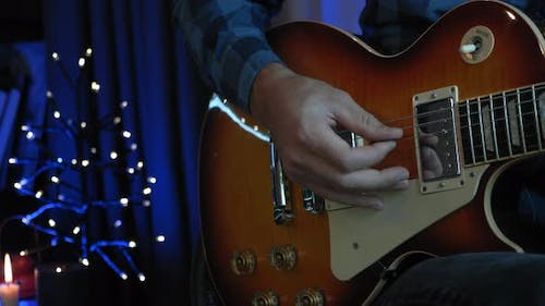 Man hand is playing on guitar strings with guitar pick in dark room with blurry lights on background