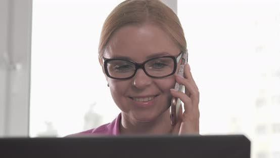 Blonde Beautiful Woman in Glasses Talking on the Phone and Looking at Camera