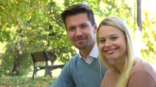 Thumbnail for A Young Attractive Couple Smiles at the Camera in a Park on a Sunny Day - Closeup
