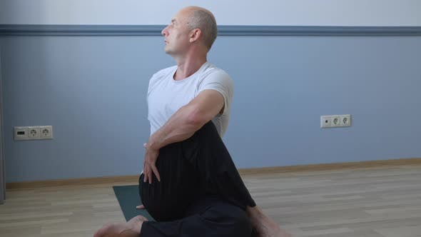 Thumbnail for Mann praktiziert Yoga und sitzt in Twist Pose zu Hause